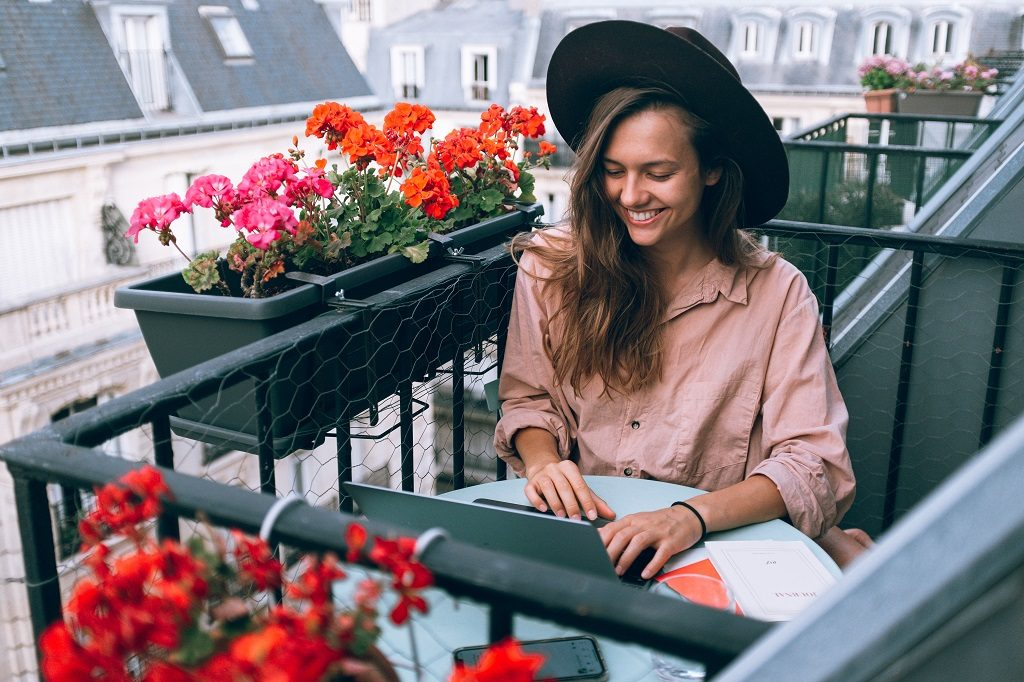 Girl sitting and working with her personal writer on balcony