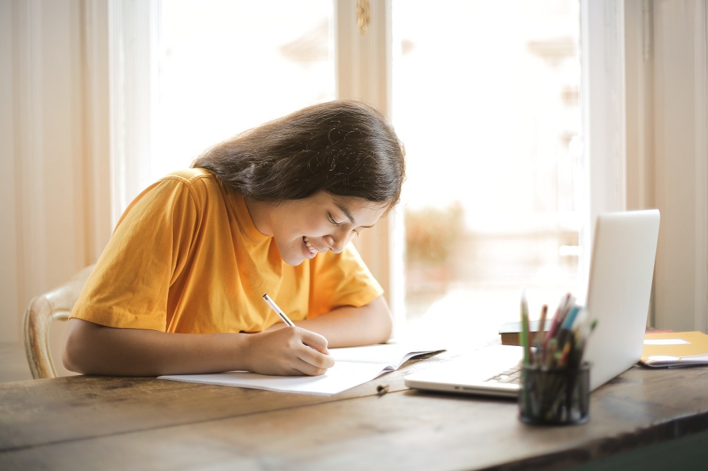 Student girl writing essay in her notebook.